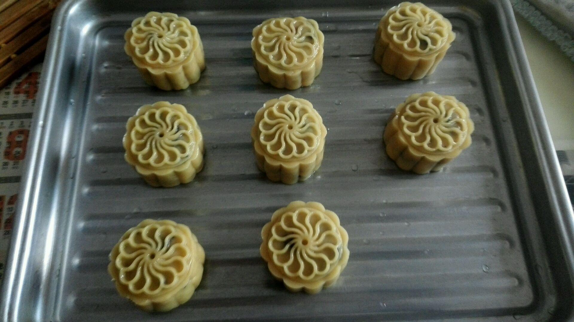 做饼的制作,将包好的月饼用模具压成不同的形状,可在模具中抹些花生