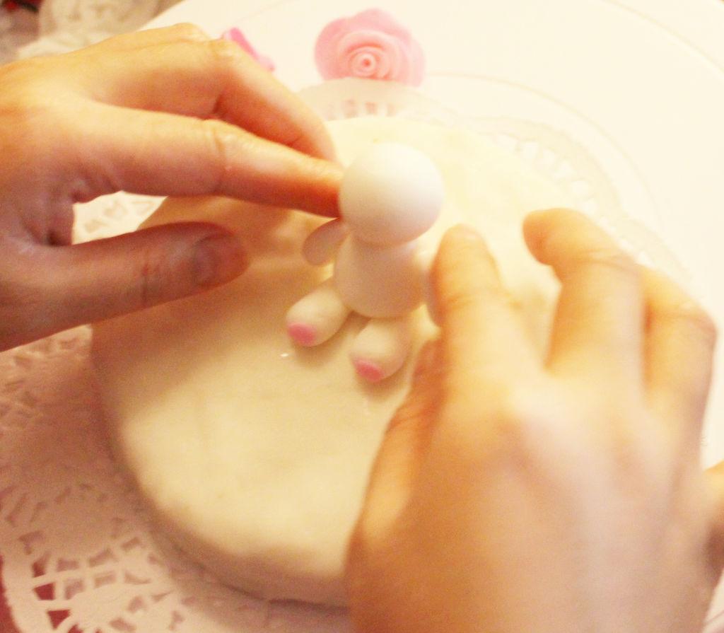 4. 然后就可以取出干佩斯先做出两条腿粘在蛋糕上,我用的是清水粘的,然后搓出一个兔子的身子,最好是要略比兔子头小一点,兔子脑袋大一点会显的更萌一点,把身子插上一根牙签再插到蛋糕里,这样更稳。身子放在腿上就行。然后再做出两个小手臂来粘上之后,再做出头,头也用牙签固定在身子上。