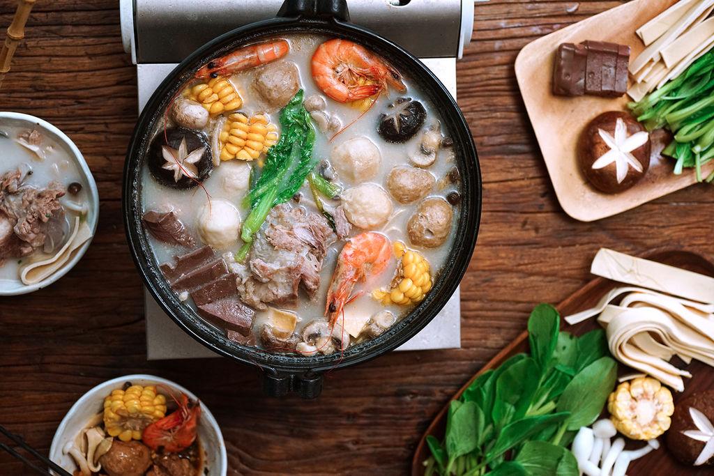 天越来越冷了,想吃暖暖的东西又不想动时,火锅简直是最好最方便的选择。 买来喜欢的食材涮一涮,就能解决丰盛的一顿。不仅吃不腻,不同的锅底可以让一个冬天都不重样。所以我决定干脆做个火锅特辑,连发几个适合宅在家里吃的火锅。 其中做法最简单的,大概就是骨汤火锅了。 买来筒骨炖了用来做底,放玉米香菇大虾让它更鲜甜,除了加一点盐,不再需要任何调味料。醇香的一大锅,重口的需求则用蘸料来满足。 看着汤水咕嘟冒烟变的浓白,窗外的凉意也变的柔和起来。