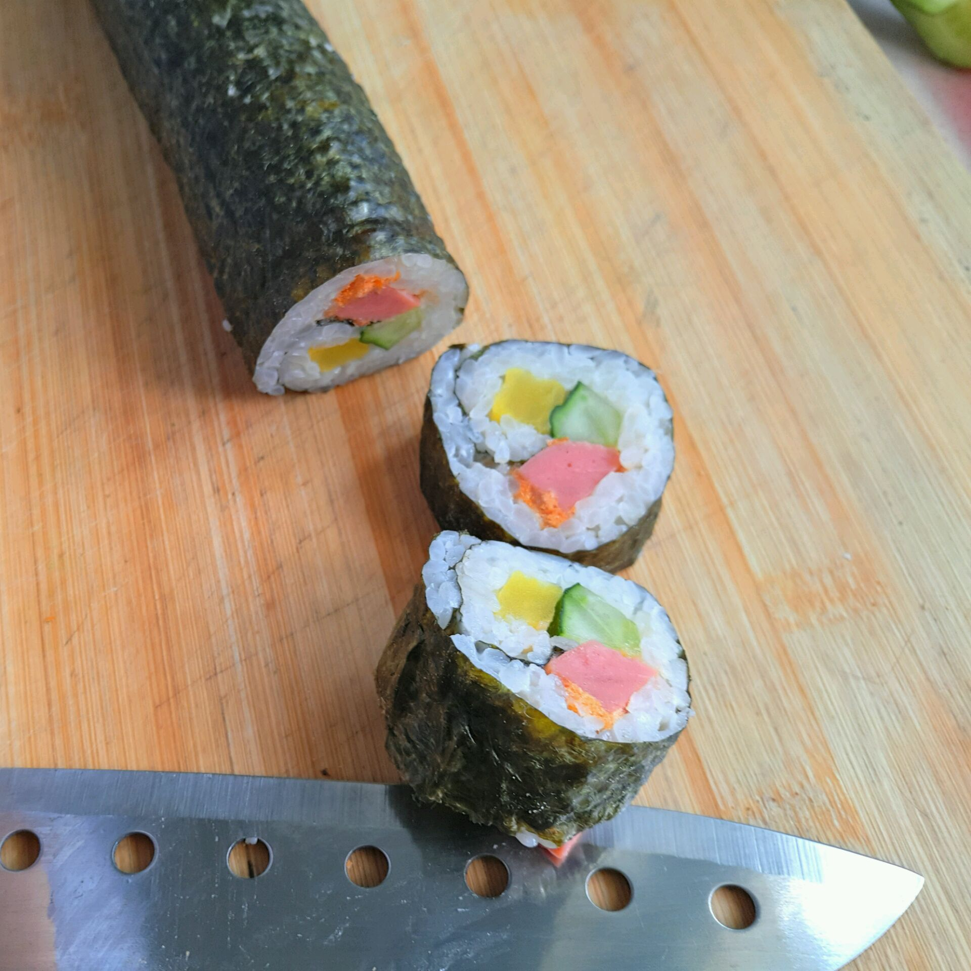 寿司的做法步骤 铺上用醋拌好的饭,黄瓜,火腿肠,调味萝卜