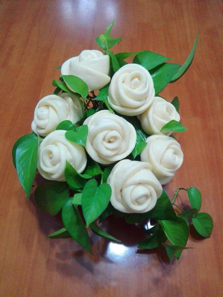 1.每一朵玫瑰花都是6个为一组,这样出来的玫瑰花层次感最漂亮。 2.每一个面片都要擀得厚薄一致,且厚度为0.5cm,这样出来的玫瑰花比较漂亮。 3.每一个面片都要撒上适量面粉,这样面片之间不会紧紧的黏在一起,便于后期的发酵,否则就会影响发酵的效果,成品会发的不好。 4.将玫瑰花瓣稍稍往外翻一点,能利于更好的发酵,否则就会变成玫瑰花苞了。