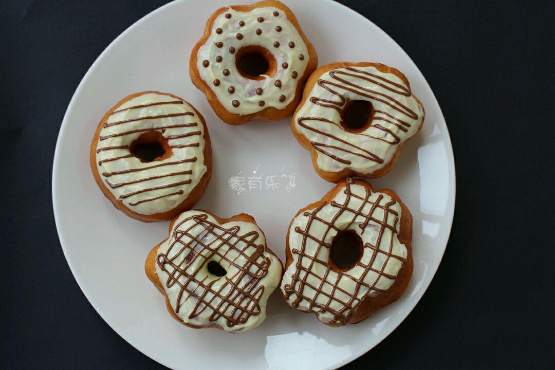 甜甜圈表面沾上巧克力,并用黑巧克力画上喜欢的花型图片