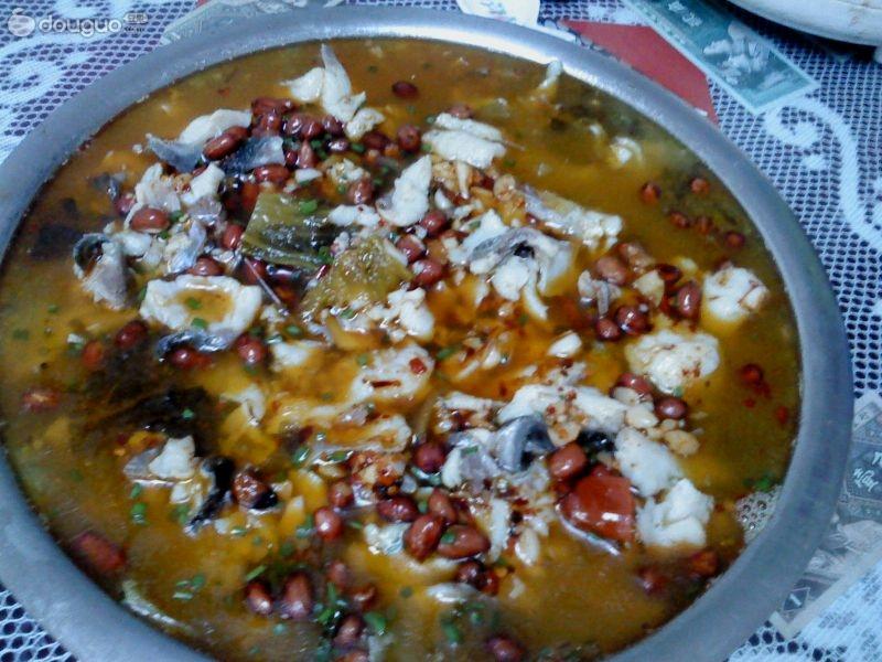 2. 切好的鱼片用料酒和少许盐,山芋粉腌制一下,接下来把鱼骨和鱼尾放在汤锅里炖,捞去漂浮物,倒入少许料酒,放入生姜片一起熬汤。一边熬汤时,一边炸几十颗花生米备用。蒜头捣成末备用,香菜切断。等汤熬成奶白色时,把自己腌的酸菜放下去,因为酸菜是辣的,我自己腌的酸菜。放入酸菜煮五分钟,等锅开后,把鱼片放入锅里,用筷子把鱼片快速拨散开,煮三十秒就好了,煮太老不好吃。另起锅少热倒入油放入花椒和红辣椒炸出辣椒油,捞吃辣椒和花椒,在锅里洒上香菜和蒜泥和花生米,最后淋上熬好的辣椒油就好了。