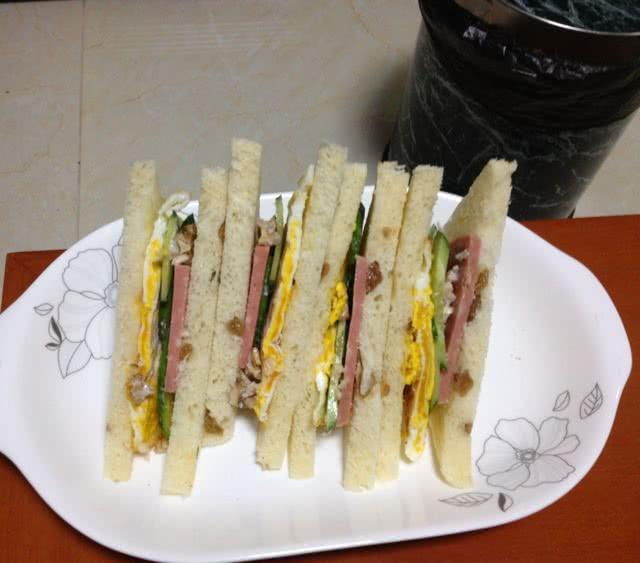 简易三明治的做法步骤 2. 切好需要用的黄瓜和火腿平铺在土司上. 3.