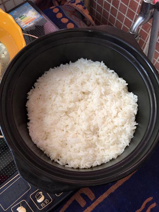那是因为,饭是电饭锅煮的,现成的.煲仔抹了一层油,再把米饭铺上去.