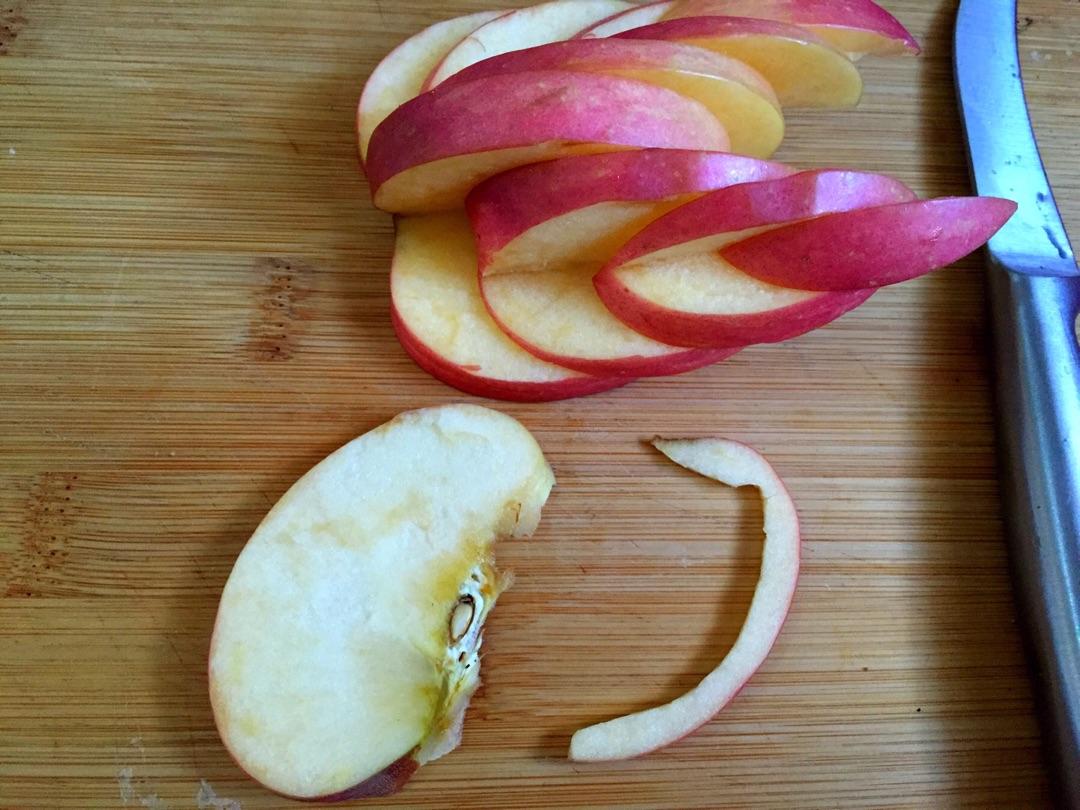 将薄片的苹果中间切开,取一半利用苹果的天然弯曲刻出天鹅的长脖子和图片