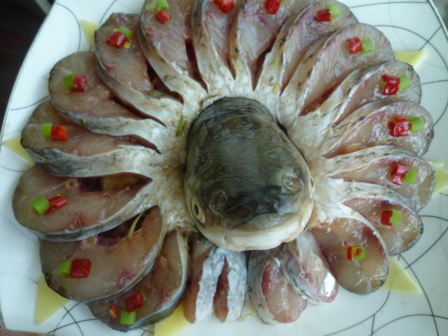 盘身下垫葱姜丝,把鱼摆盘鱼头放中间,用辣椒装饰.图片
