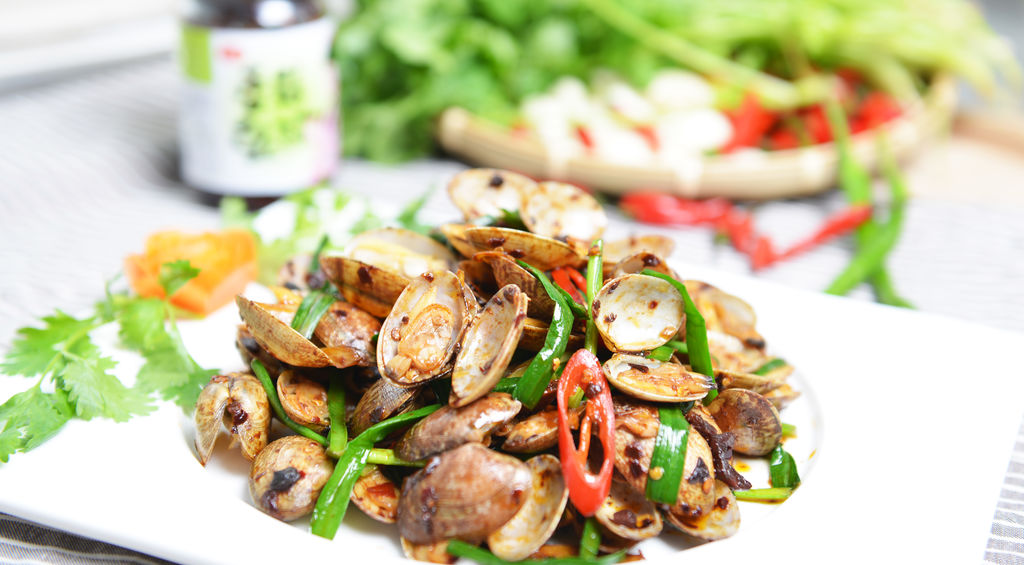 """花蛤( g ),俗称""""文蛤"""",贝类中的珍品,因贝壳表面光滑并布有美丽的红、褐、黑等色花纹而得名,是近海地带的常见贝类海产品。 以往只能在海边才能吃到的新鲜玩意儿,不知从何时起已经成为街边烧烤小摊、海鲜大排档里的一道必点招牌菜。 夏天的傍晚,爆炒花蛤的那种特殊香味在大街小巷中飘荡,无孔不入,行人对这种香味的抵抗力几乎为零,对我这种资深吃货来说,更是招架不住呢~ 许多人对花蛤滋味难以割舍,想吃但怕街边小摊处理的不卫生、不干净,不吃又不自觉地想念。 今天小北就来教大家做这道爆炒花蛤,其实看似复杂的花蛤做法很"""