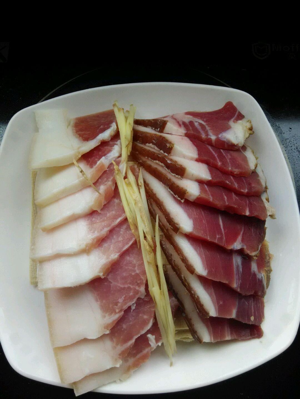 把切好的咸肉和熏肉片,码放在百叶上,加生姜,料酒,洒少许糖.图片
