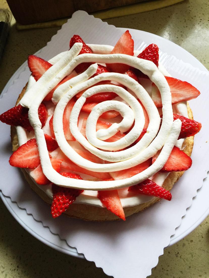 8. 将最顶上的一片蛋糕做底,戚风底做顶(因为底部最平整)将打发好的淡奶油(淡奶油200g+20g糖粉打发)入裱花袋,剪刀剪1cm口,挤在第一层蛋糕胚上。中间抹平,四周可以挤出来一点,这样装饰上水果会更好看。