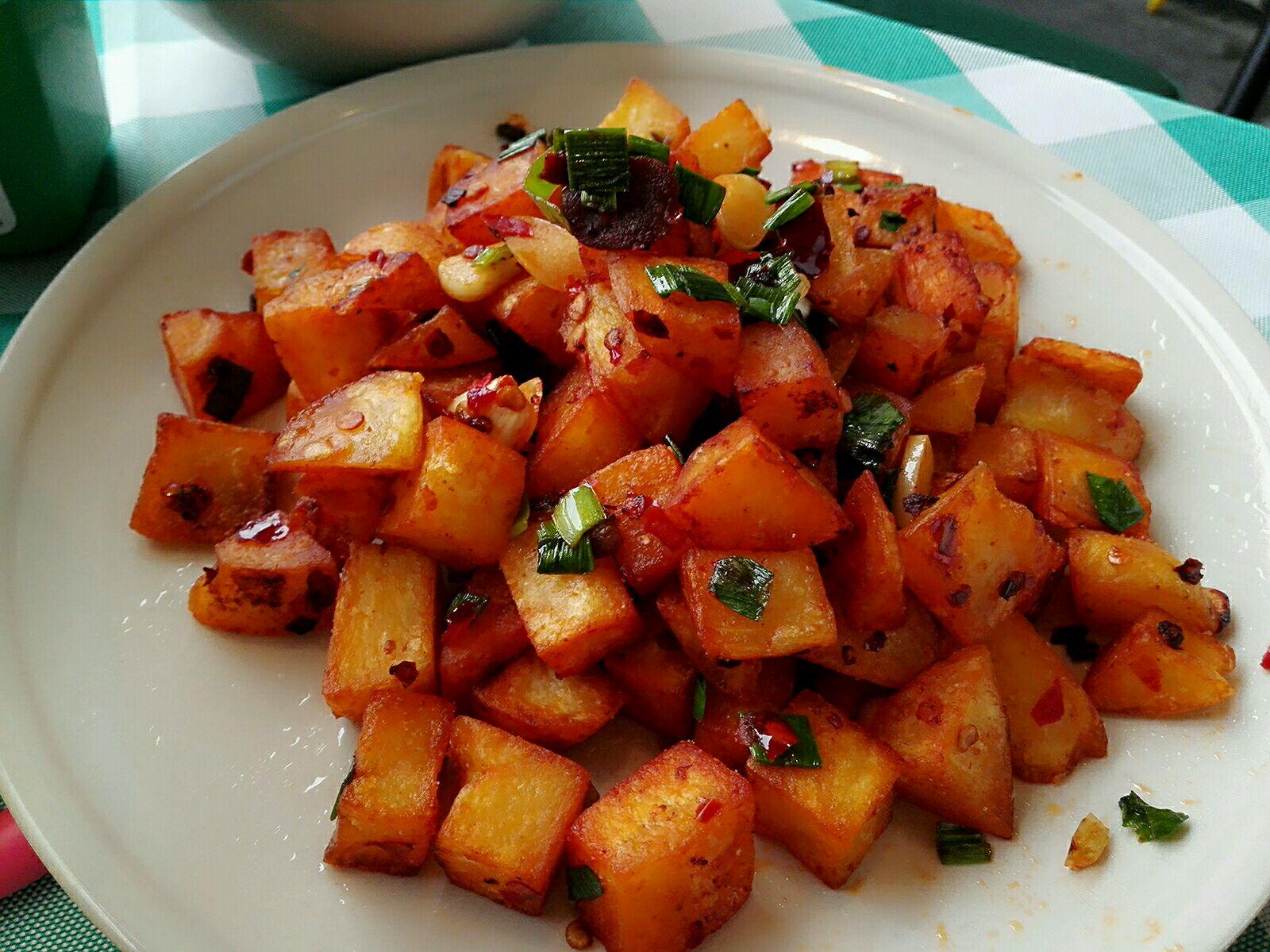 1. 一:土豆洗干净,去皮,切成方丁。 二:往锅里加入水,烧开之后煮土豆,一定要把土豆煮熟。煮熟之后,捞出来过一下冷水,让土豆冷却下来。 三:往锅里加入食用油,把煮过之后的土豆放在锅里油炸,炸到外面一层为金黄色的,就可以捞出来备用了。 四:锅里放入少许食用油,油温起来之后放入一勺郫县豆瓣,放入切好的蒜头和生姜(两三小块就行了)加入少量白糖 五:步骤四炒出香味之后,把之前炸过的土豆放入锅里翻炒,然后加入花椒粉,孜然粉,适量的鸡精,最后加入葱花和蒜叶就可以出锅了。
